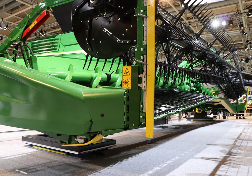 The Deere HDX draper header is hinged to better follow rolling terrain and has optional vertical knives for heavy canola crops.